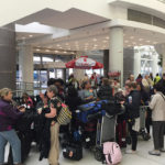 The travelers gather at the airport.